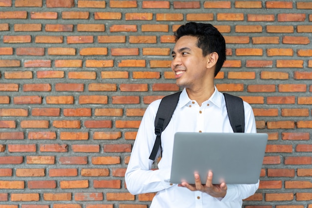 Estudiante latino usando laptop en el edificio de ladrillo campus