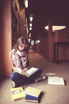 Estudiante leyendo un libro en el pasillo de la biblioteca