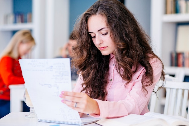 Estudiante leyendo notas en la biblioteca