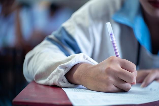 Estudiante leyendo y tomando examen con estrés.