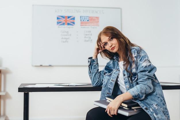 Estudiante con libros en el aula de la escuela de inglés.