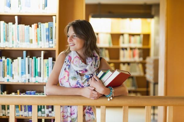 Estudiante con libros en la biblioteca