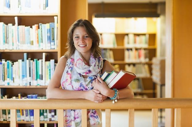 Estudiante con libros de pie en la biblioteca