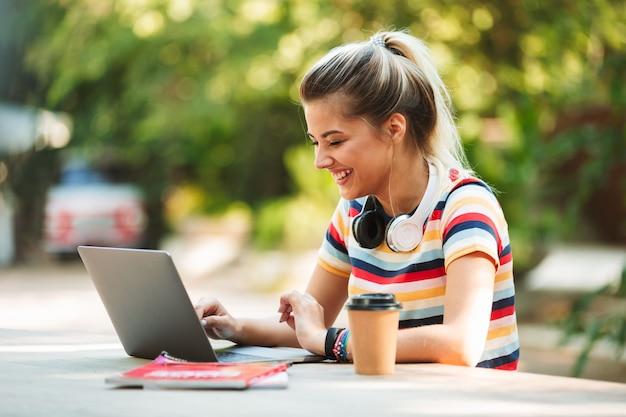 Estudiante linda joven feliz que se sienta en el parque usando la computadora portátil.