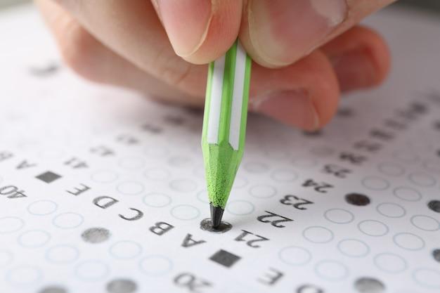 Estudiante llena la hoja de prueba de respuestas, de cerca