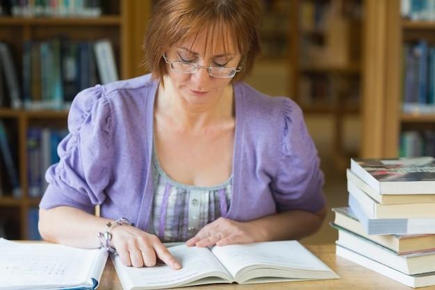 Estudiante madura que estudia en el escritorio en la biblioteca