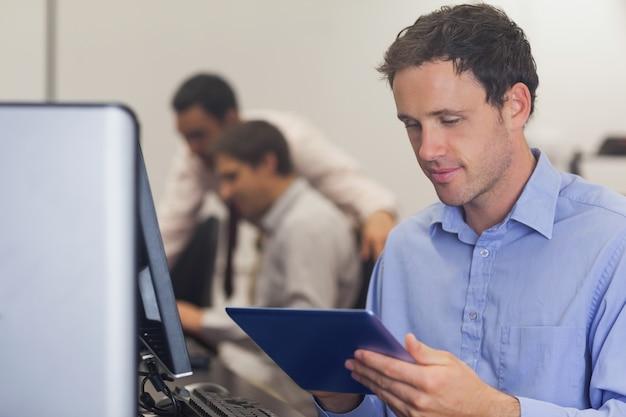 Estudiante maduro masculino que trabaja con una tableta
