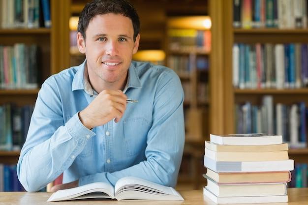 Estudiante maduro sonriente que estudia en el escritorio de la biblioteca