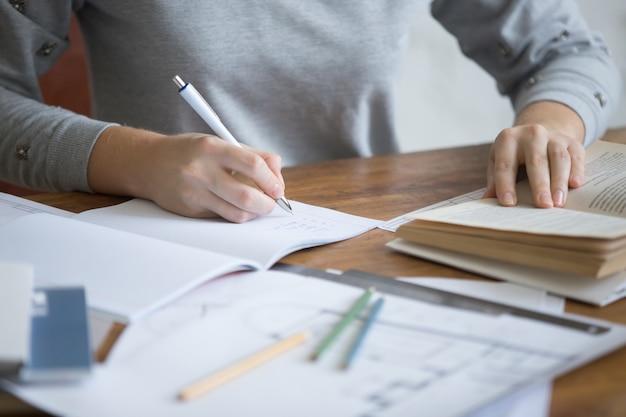 Estudiante manos femeninas realizar una tarea escrita en un copybook