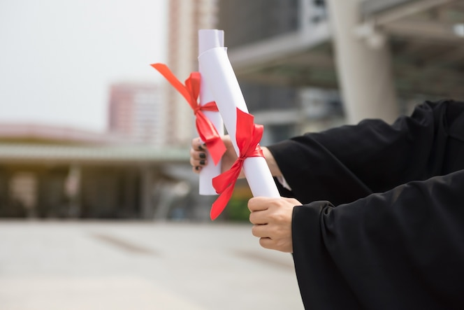 Estudiante manos sosteniendo diploma