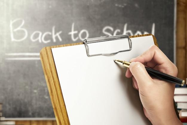 Estudiante manos sosteniendo portapapeles y escribiendo en el aula