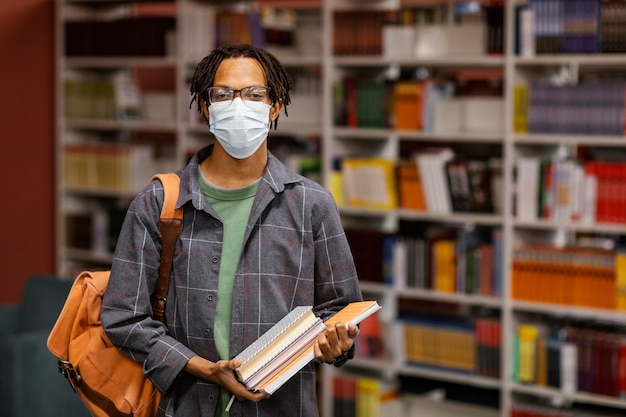 Estudiante con una máscara médica en la biblioteca.
