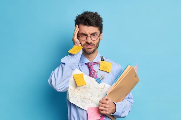 El estudiante masculino sin afeitar grave e intenso tiene dolor de cabeza debido a un largo trabajo ocupado preparándose para el examen de matemáticas o hace que el proyecto tenga fecha límite lleva trabajos con sumas escritas
