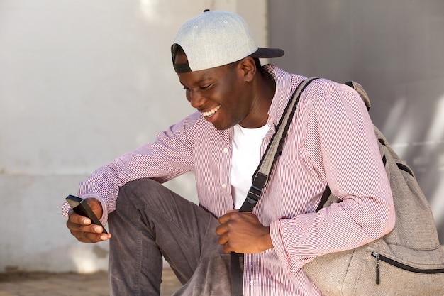 Estudiante masculino africano joven con el casquillo que sonríe y que mira el teléfono móvil