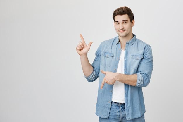 Estudiante masculino alegre guapo apuntando hacia arriba y hacia abajo en pancartas