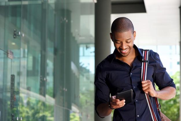 Estudiante masculino caminando en la ciudad con tableta y bolsa