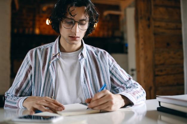 Estudiante masculino enfocado en vasos en el escritorio tomando notas en el cuaderno, anotando pensamientos e ideas, preparándose para una prueba o examen.