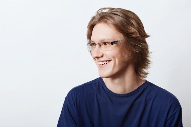 Estudiante masculino con expresión inteligente que tiene buen humor, sonriendo agradablemente mientras se regocija por su éxito en el examen. empresario masculino sonriente en camiseta casual mirando a un lado con expresión alegre
