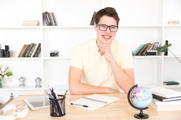 Estudiante masculino feliz que se sienta con el cuaderno vacío