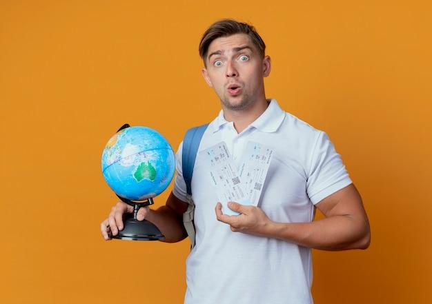 Estudiante masculino hermoso joven sorprendido que lleva el bolso trasero que sostiene los boletos y el globo aislado en naranja