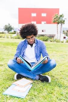 Un estudiante masculino joven afroamericano que se sienta en el césped que lee el libro