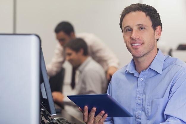 Estudiante masculino que sostiene una tableta que se sienta delante de la computadora