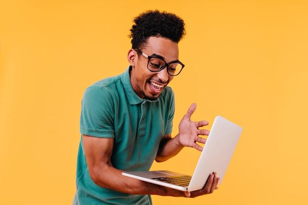 Estudiante masculino rizado sorprendido que mira la pantalla del ordenador portátil. filmación en interiores de freelancer africano lleva gafas.