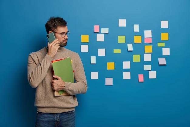 Estudiante masculino serio lee publicaciones pegajosas en la pared azul, gira a la derecha tiene conversación telefónica sostiene libros de texto coloridos vestidos casualmente discute la preparación del examen.