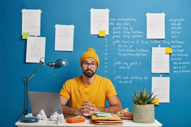 Estudiante masculino sorprendido posa en el escritorio en casa u oficina, usa una computadora portátil para buscar un curso de educación en línea, navega por el sitio web de aprendizaje a distancia