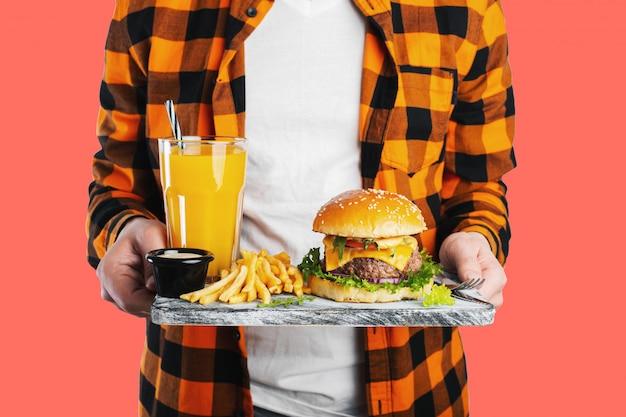 Un estudiante masculino está sosteniendo el tablero con una hamburguesa fresca.