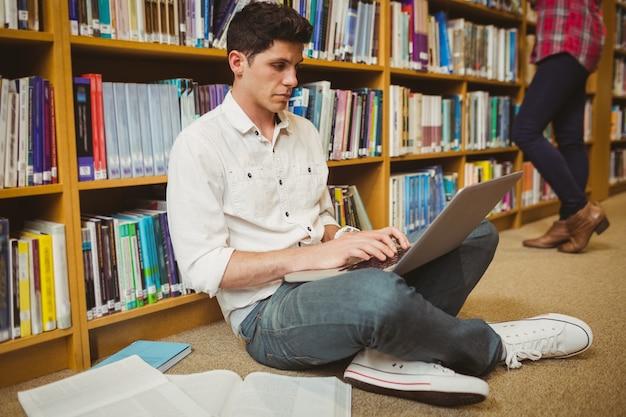 Estudiante masculino trabajando en el piso en la biblioteca