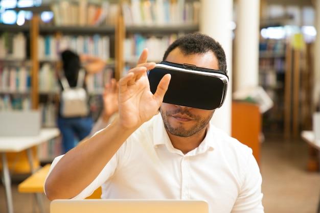Estudiante masculino usando simulador de realidad virtual para el entrenamiento