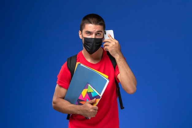 Estudiante masculino de vista frontal en camiseta roja con mochila con máscara con archivos de cuaderno hablando por teléfono sobre el fondo azul.