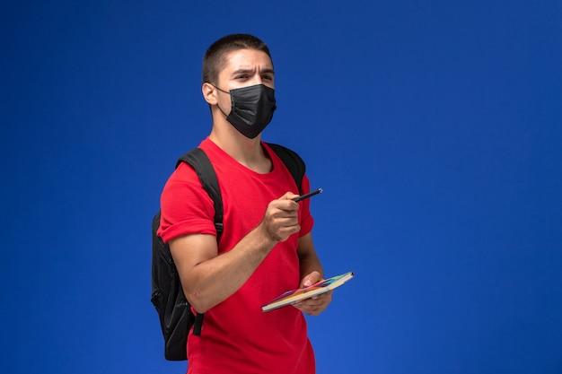 Estudiante masculino de vista frontal en camiseta roja con mochila en máscara estéril negra sosteniendo bolígrafo y cuaderno sobre el escritorio azul.