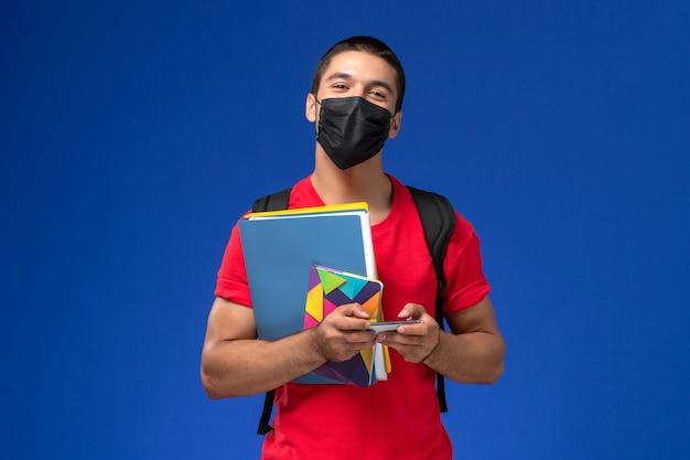 Estudiante masculino de vista frontal en camiseta roja con mochila con máscara sosteniendo archivos y usando su teléfono en el fondo azul.