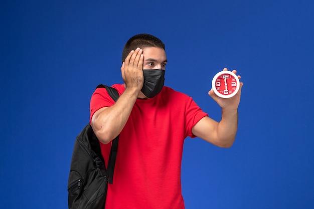 Estudiante masculino de vista frontal en camiseta roja con mochila con máscara sosteniendo relojes en el escritorio azul.