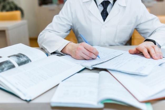 Un estudiante de medicina para libros de texto. el estudio de la cirugía por un hombre con corbata en la biblioteca. enfermero. copia espacio