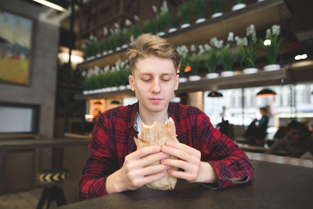 Un estudiante con una mirada hambrienta mira el emparedado en sus manos.