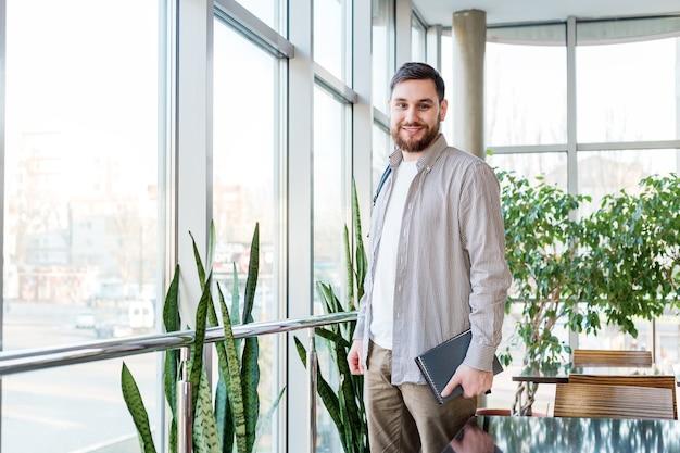 Estudiante con mochila, cuadernos, libros de texto en el campus universitario de reabrir. adolescente caucásico, sonriente apuesto hombre barbudo junto a la ventana. freelancer en oficina de coworking moderna con plantas.