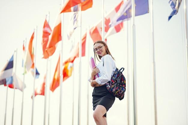Estudiante con una mochila en una escena de banderas