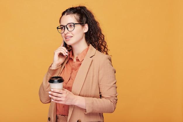 Estudiante morena bastante joven con un vaso de café y un teléfono inteligente hablando con alguien en el descanso sobre la pared amarilla en aislamiento