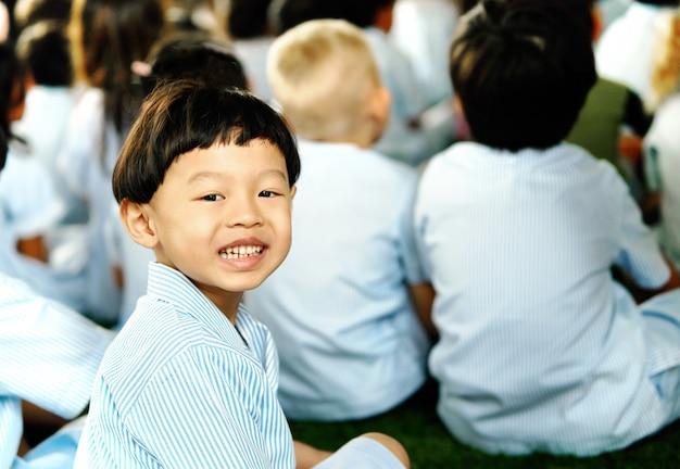 El estudiante del muchacho se sienta en fila en alumnos