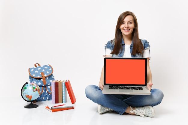 Estudiante mujer bonita joven que sostiene la computadora portátil de la pc con la pantalla vacía negra en blanco que se sienta cerca de los libros escolares de la mochila del globo aislado
