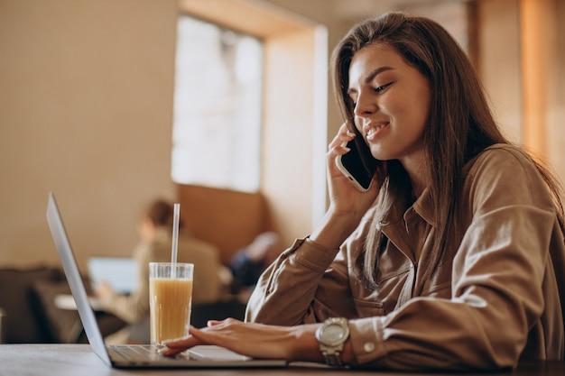 Estudiante mujer estudiando en un portátil en un café