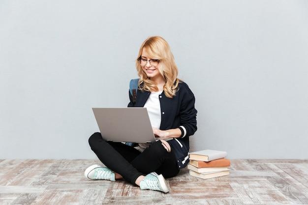 Estudiante de mujer joven alegre que usa la computadora portátil.