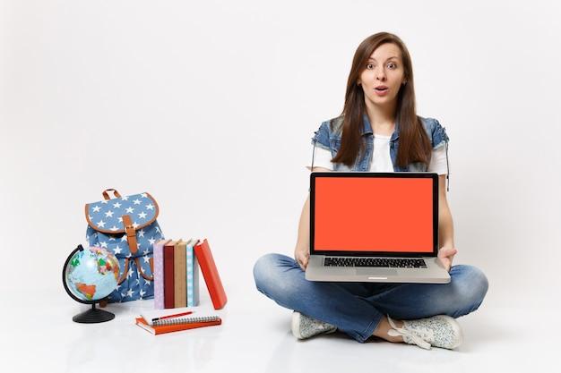 Estudiante mujer joven emocionada que sostiene la computadora portátil con la pantalla vacía en blanco negro sentado cerca de los libros escolares de la mochila del globo aislado