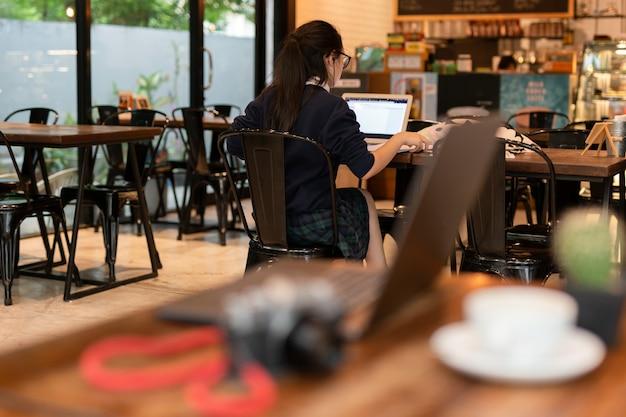 Estudiante de mujer joven que trabaja con la computadora portátil en café.
