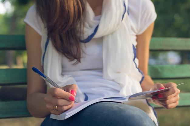 Estudiante de mujer joven sentado en un banco en el parque