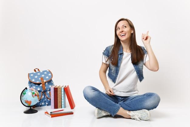 Estudiante mujer sonriente pensativa en ropa de mezclilla soñando, apuntando con el dedo índice hacia arriba, sentado cerca del globo, mochila, libros escolares aislados