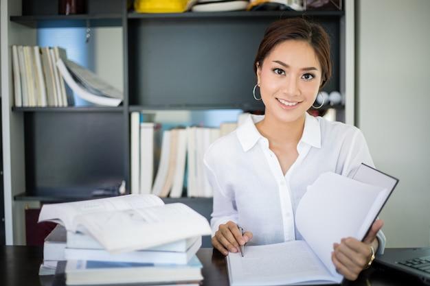 Estudiante de mujeres asiáticas sonriendo y leyendo un libro para el examen final en casa